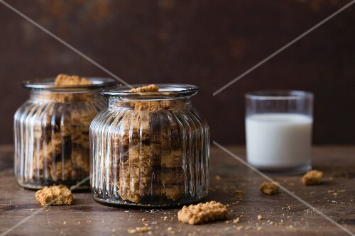 Cookies in glass jars with a glass of milk