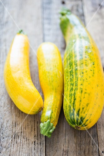 Yellow courgettes on a wooden surface