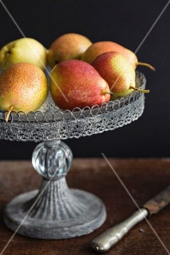 Pears on a cake stand against a black surface