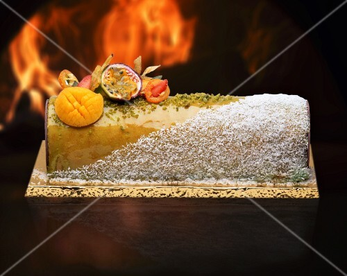 A Yule log with garnished with grated coconut and exotic fruit