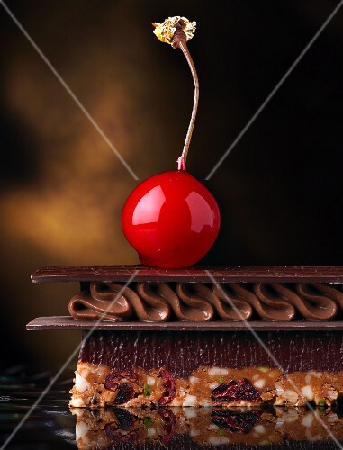 A layered chocolate dessert topped with a candied cherry (close up)