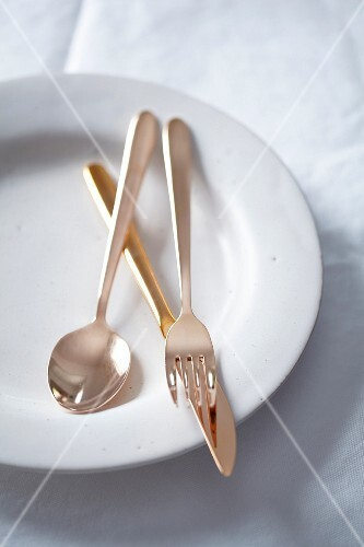 Copper-coloured cutlery on a white plate