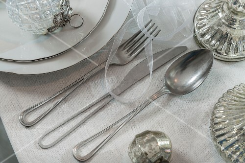 Silver cutlery with centres of handles removed on set table