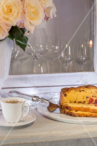 Cut fruit cake and cake slice next to cup of coffee