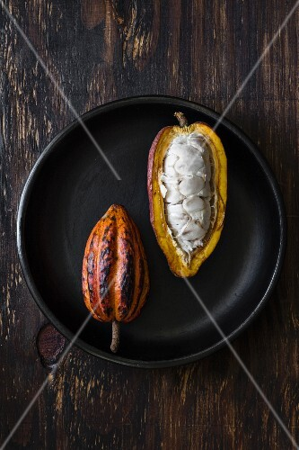Two cacao pods, whole and sliced open (seen from above)