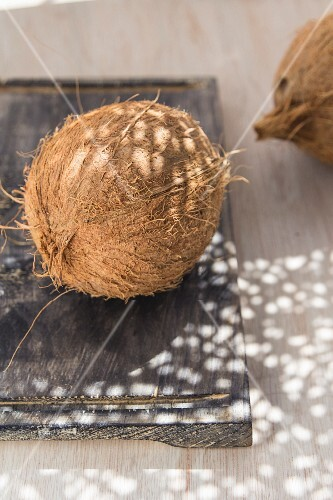 A whole coconut on a wooden board in sunlight