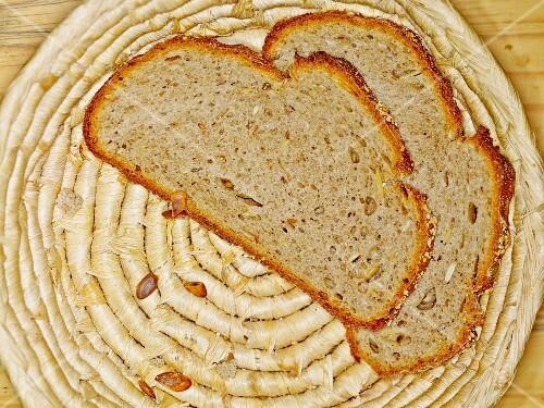 Two freshly cut slices of pumpkin and spelt bread in a breadbasket