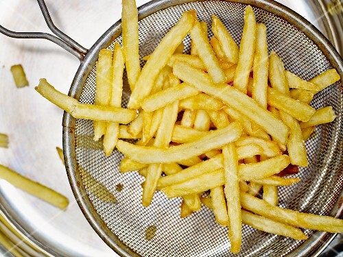 Freshly fried chips in a sieve over a drainer