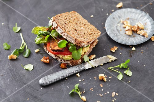 A vegan sandwich with tofu, tomatoes and watercress