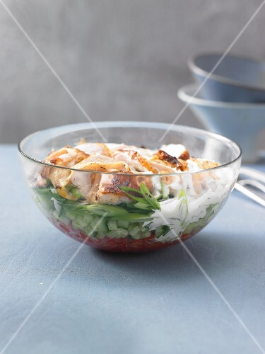 A layered salad with roast chicken, cucumber and tomatoes