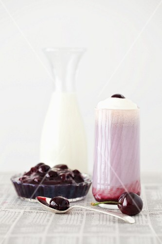 A cherry milkshake topped with whipped cream and cherry sauce