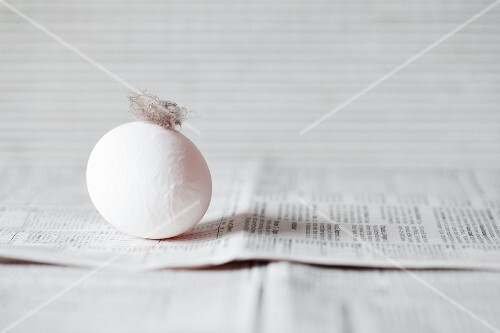 A white egg with a feather on a newspaper