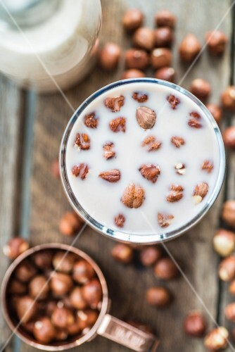A glass of hazelnut milk with hazelnuts