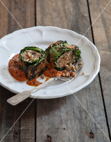 Savoy cabbage roulade filled with amaranth on a tomatoes and tahini sauce