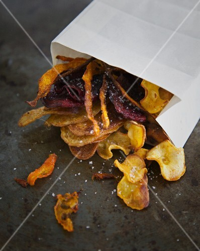 Colourful vegetable crisps with salt and a paper bag