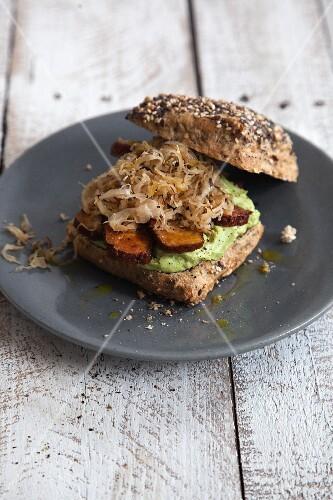 Vegan sauerkraut sandwich with smoked tofu and avocado cream