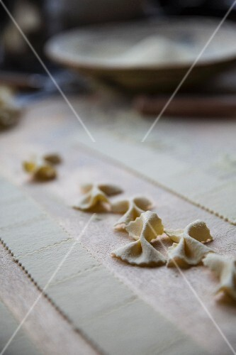 Handmade farafalle on a floured wooden table