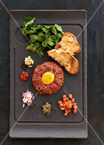 Beef tatar with an egg yolk and grilled bread