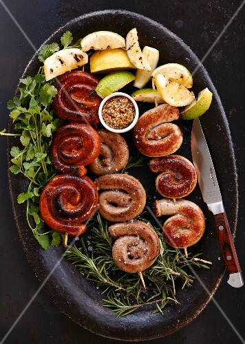 Sausage skewers with lemons on a bed of herbs