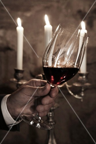 Christmas in a wine cellar: a hand holding a glass of red wine in front of a candelabra