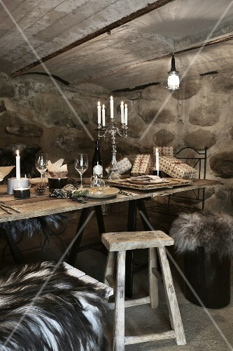 Christmas in a wine cellar: rustic wooden table set with wine and candles