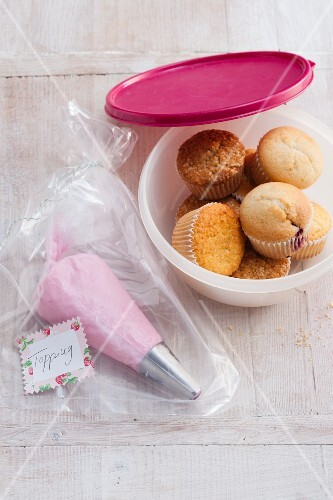 A piping bag filled with a topping in a freezer bag with muffins in a Tupperware box