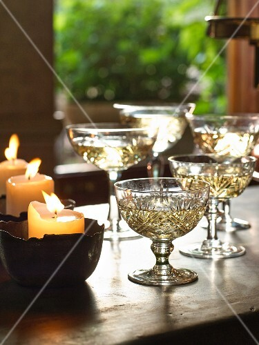 Champagne in crystal goblets next to burning candles