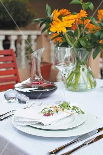 A table laid with a white cloth with a carafe of red wine and a bunch of orange flowers