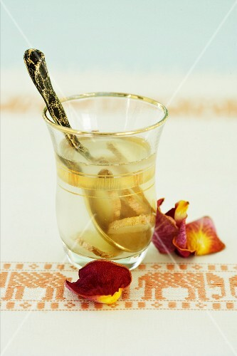 A glass of ginger water with a spoon