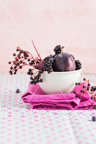 Damsons, elderberries, blackberries and blueberries in a bowl