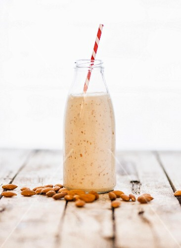 A bottle of almond milk and almonds on a wooden surface