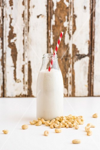 Cashew nuts and a bottle of cashew milk with a straw