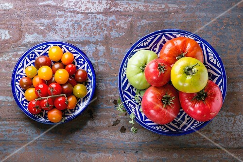 Two plates of tomatoes on a metal surface (seen from above)