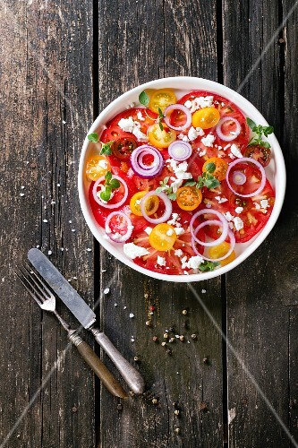 A colourful tomato salad with red onions and feta cheese on an old wooden table (seen from above)