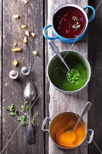 Three different types of cream soup (beetroot, pea and carrot) in old pots