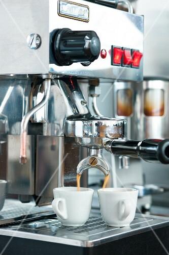 Espresso flowing into cups