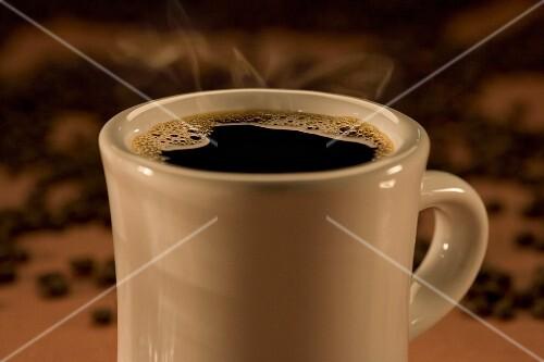 A steaming hot mug of black coffee