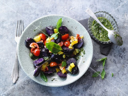 Blue potato salad with peppers and cherry tomatoes (vegetarian)