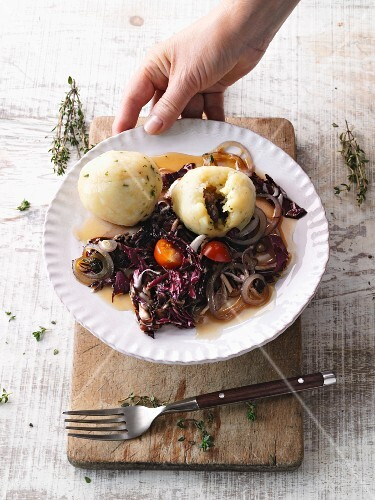 Mediterranean herb dumplings with salsiccia being served