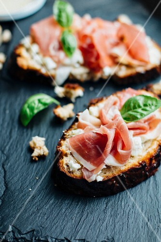 Open sandwiches topped with Parma ham and basil