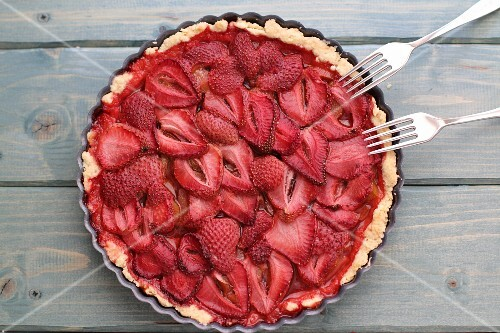 Strawberry tart in a baking tin with forks (seen from above)
