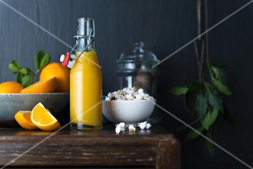 A bottle of orange juice, fresh oranges and popcorn
