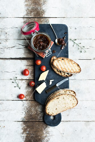 Tomato chutney in a jar and on a spoon with slices of bread and cheese