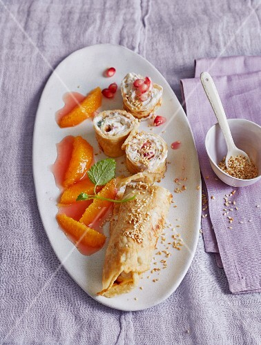 Sesame seed crepes filled with cream cheese and pomegranate seeds