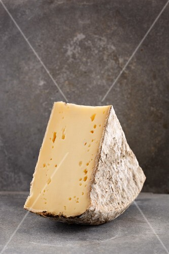 A slice of Tomme de Savoie cheese
