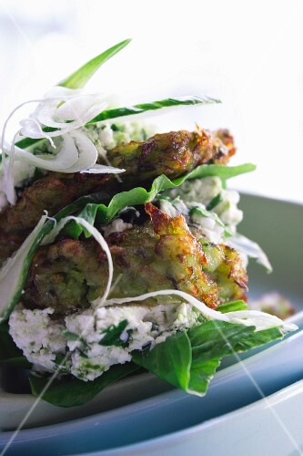Courgette fritters with goat's cheese, ricotta, spinach and cucumber slices