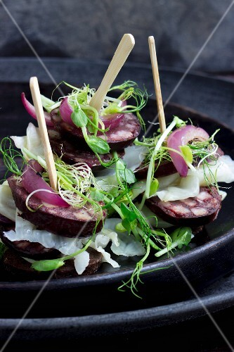 Pumpernickel millefeuilles with blood sausage, white cabbage and bean sprouts on a black plate