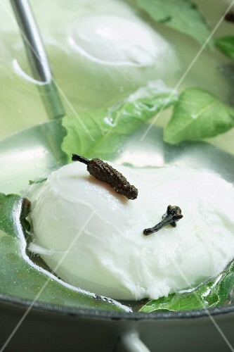 A poached egg on a draining spoon with spices