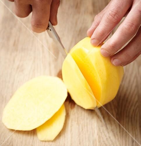 A peeled potato being sliced