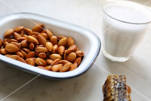 Honey comb, soften, drained almonds and a glass of almond milk